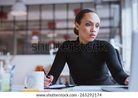 Image of african young woman working new business assignment. Female executive sitting at her desk using laptop and writing notes at office.