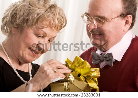 Image of aged woman opening giftbox with her husband near by