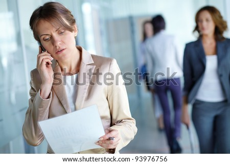 Image of agent reading document while speaking on the phone in working environment