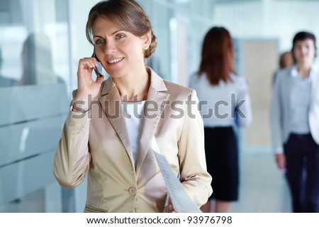 Image of agent with paper speaking on the phone in working environment