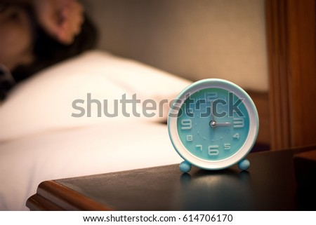 Image of alarm clock time at 3 a.m. in the morning with blurry women lay down on white bed and pillow cannot sleep hand on her head suffering from chronic insomnia #614706170