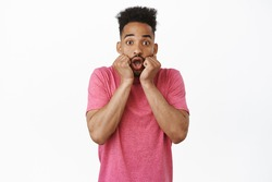 Image of amazed and excited african american guy, gasping impressed, staring thrilled at awesome big news, look surprised, receive awesome gift, white background