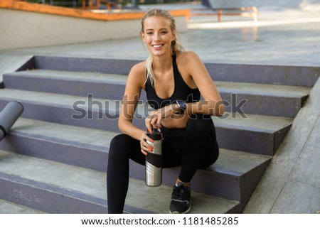 Image of amazing young sports woman outdoors holding bottle with water.