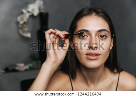 Image of an cheerful cute young beautiful woman in bathroom take care of her skin doing makeup with lash mascara.