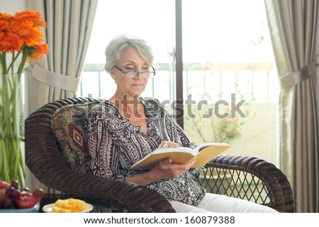 Image of an elegant senior lady sitting in an armchair and reading a book #160879388