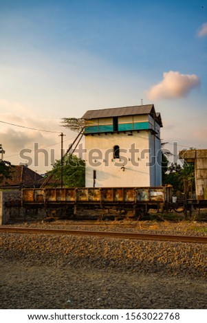 Image of an old and rusty wagon with used water tower building and clear blue sky as background.  #1563022768