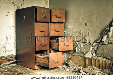 Image of an old rusty filing cabinet in a derelict abandoned building near a crumbling wall with peeling paint.