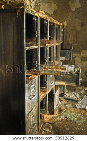 Image of an old rusty filing cabinet in a derelict abandoned police station covered in debris.