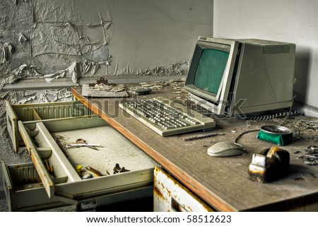 Image of an old, vintage computer in a derelict abandoned police station covered in debris and dust.