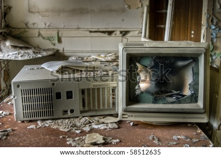 Image of an old, vintage destroyed computer in a derelict abandoned police station covered in debris and dust.