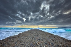Image of an outfall with waves and stormy clouds and sunset, Jersey Channel Islands