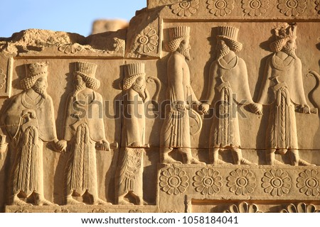 Image of ancient Persian ambassadors. Bearded men facing each other and holding hands.  An ancient relief on the walls of the ruined Persepolis city.Iran.