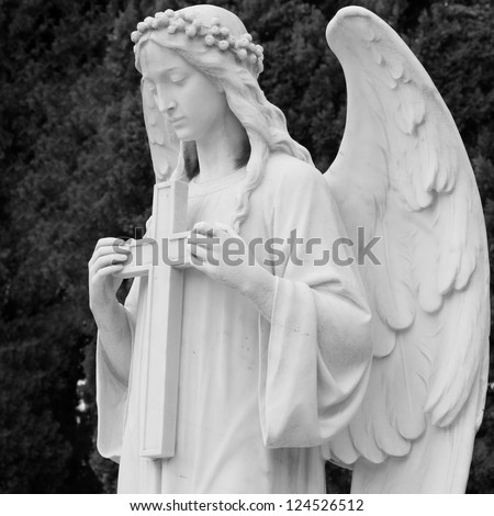 image of angel  holding a cross, detail of historic tomb on monumental cemetery in Italy, Europe