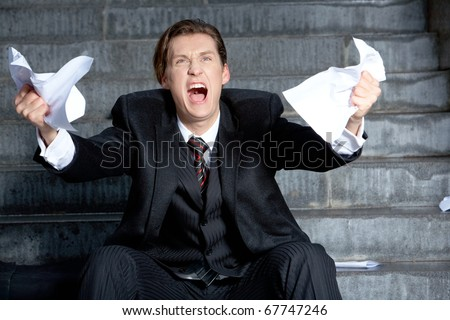 Image of angry businessman with papers in hands raising its