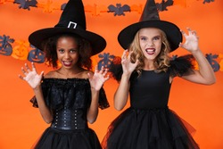 Image of angry multinational girls in black halloween costumes scratching and frightening isolated over orange pumpkin wall