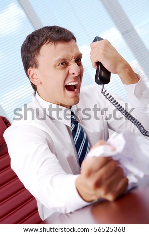 Image of annoyed boss losing his temper and screaming into phone receiver
