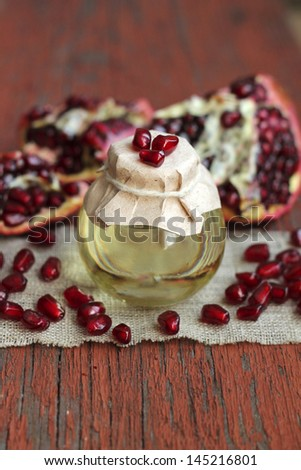 Image of aromatic pomegranate oil in glass bottle, close-up