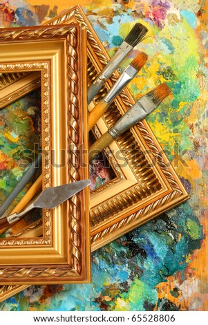 Image of artist's palette, paintbrushes and art frames