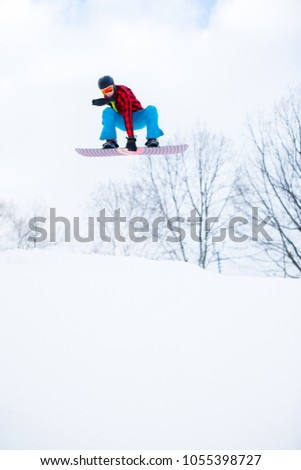 Image of athlete wearing helmet with snowboard jumping in snowy resort #1055398727