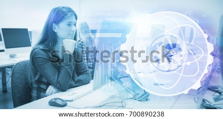 Image of atom interface against serious student working on computer