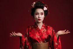 Image of attractive asian geisha woman in traditional japanese kimono hesitating isolated over red background