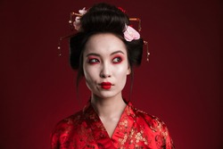 Image of attractive asian geisha woman in traditional japanese kimono isolated over red background