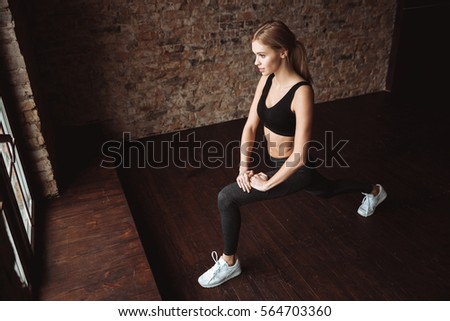 Image of attractive fitness lady make sport exercises in gym. Look aside.