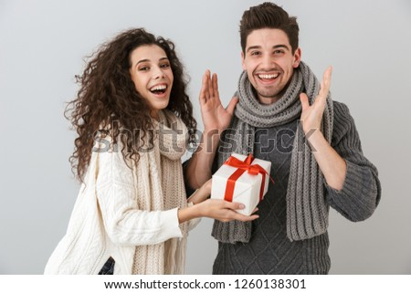 Image of attractive man and woman rejoicing while standing with present box isolated over gray background