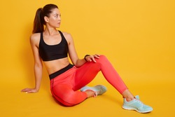 Image of attractive woman wearing sports bra and leggins, shows slim belly and press, sitting on floor and looking aside, posing isolated overe yellow background. Sport and healthy lifestyle concept.