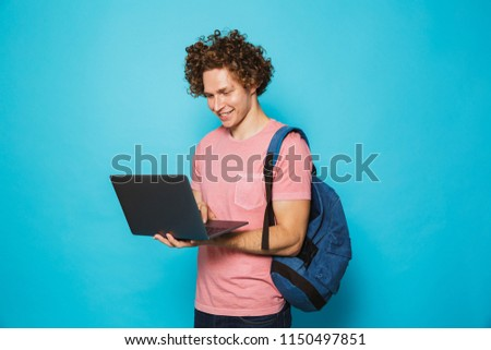 Image of attractive young guy with curly hair wearing casual clothing and backpack holding and using open laptop isolated over blue background