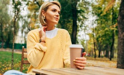 Image of attractive young woman drinking coffee at the terrace cafetaria in the park. Blonde female in the city street drinking a hot beverage, looking at one side. Pretty girl with a cup of coffee.
