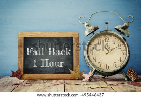 Image of autumn Time Change. Fall back concept. Dry leaves and vintage alarm Clock on  rustic wooden table #495446437