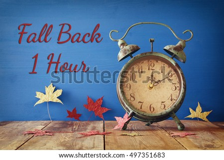 Image of autumn Time Change. Fall back concept. Dry leaves and vintage alarm Clock on  rustic wooden table #497351683
