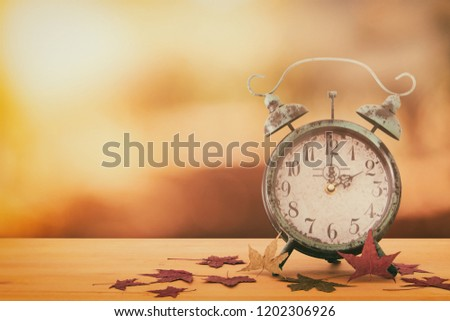 Image of autumn Time Change. Fall back concept. Dry leaves and vintage alarm Clock on rustic wooden table #1202306926