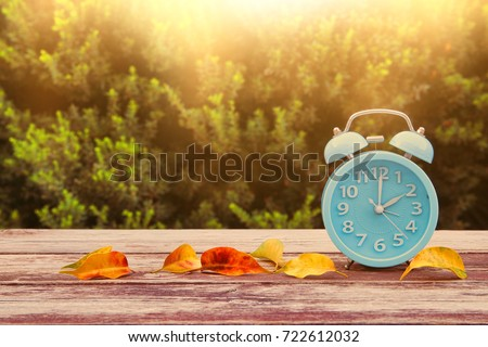 Image of autumn Time Change. Fall back concept. Dry leaves and vintage alarm Clock on wooden table outdoors at afternoon #722612032