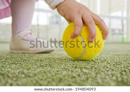 Image of baby catching tennis ball. Learning sport from birth.