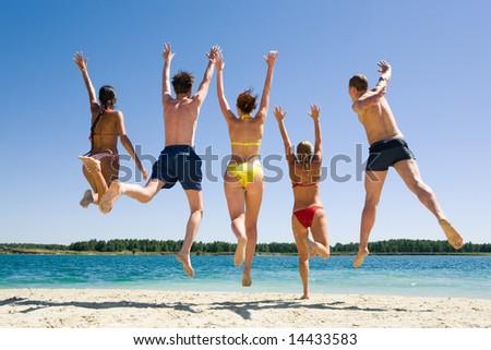 Image of backs of joyful friends jumping on the beach