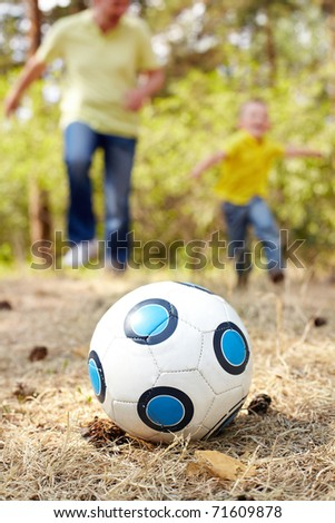 Image of ball on ground in park with running father and son at background