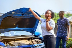 image of beautiful african lady with smart phone in front of an opened bonnet of a car, with guy bit blurred at the back- transportation concept