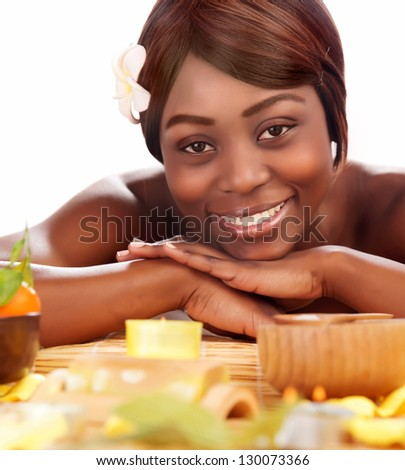 Image of beautiful afro female with franjipani flower in head enjoying dayspa, american woman relaxed in luxury spa salon, skin care, healthy lifestyle, pampering, vacation and wellness concept