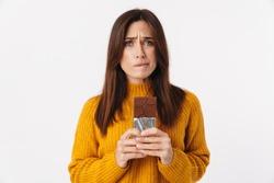 Image of beautiful brunette adult woman hesitating while holding chocolate bar isolated over white background