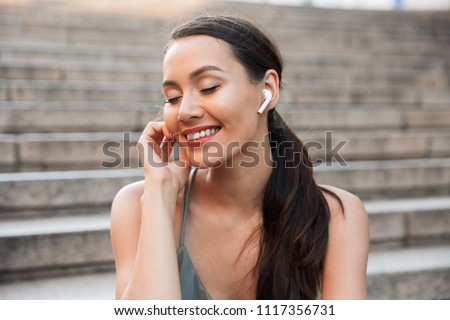 Image of beautiful brunette woman 20s with dark hair in ponytail sitting on street stairs on summer day while listening to music via bluetooth earbud Stock photo ©