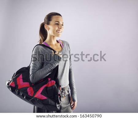 Image of beautiful caucasian female athlete with gym bag looking away smiling. Young woman in sportswear carrying gym bag looking at copyspace.