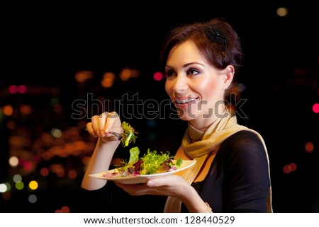 Image of beautiful female eating salad on the party, night lifestyle, attractive woman have dinner in restaurant outdoor, girl wearing dress holding in hand plate with meal, holiday celebration