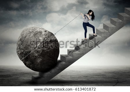 Image of beautiful female entrepreneur carrying big stone with a chain on the stair Сток-фото ©