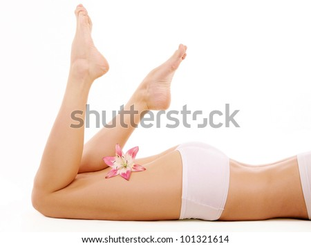 Image of beautiful female legs with lily isolated on a white background