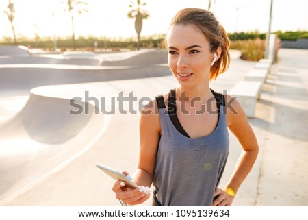 Image of beautiful fitness woman in sportswear talking or listening to music on mobile phone using wireless white earpod in skate park at sunrise