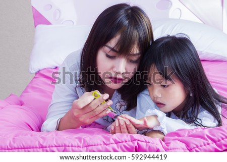 Image of beautiful mother cutting fingernail her daughter while lying on the bed while