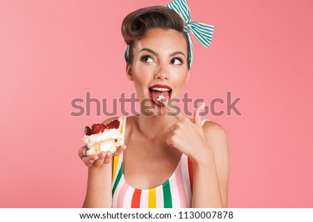 Image of beautiful pin up woman isolated over pink wall background holding cake.