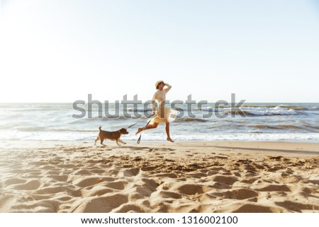 Image of beautiful woman in straw hat running with her brown dog along the coast